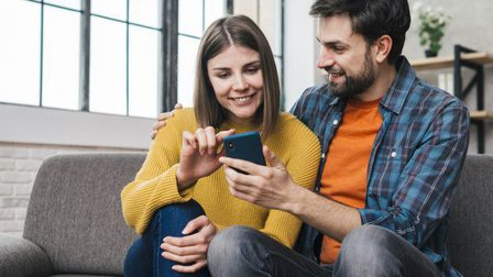 Young-couple-sitting-together-sofa-using-mobile-phone_23-2148152831_thumb_main
